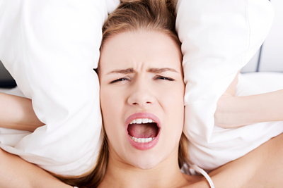 woman covering ears with pillow