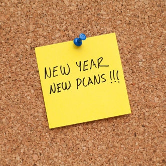 yellow post it note that says New Year New Plans pinned to bulletin board