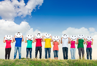 people standing with smiley face drawings over their faces