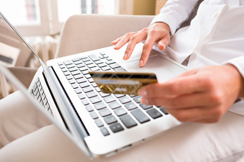 person with laptop making an electronic payment for HOA fees