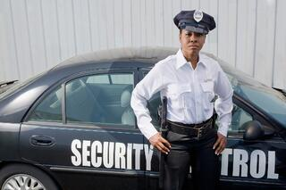 security patrol officer standing next to patrol car