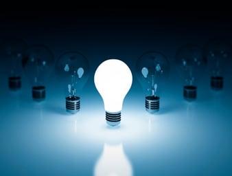 one illuminated light bulb in a row of unlit bulbs