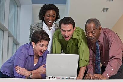 business_executives_using_laptop_and_smiling