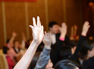 raised hands at a meeting