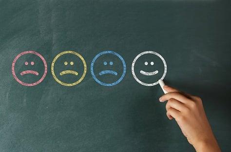 sad and happy smileys on blackboard