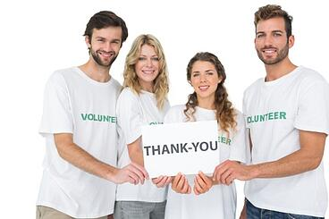 volunteers holding thank you sign