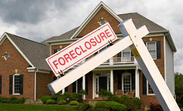 foreclosure sign posted in front of brick house