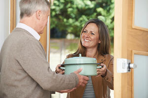 woman bringing meal to neighbor